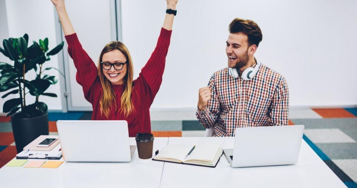 Dos jovenes celebrando y estudiando en su curso de inglés creando un buen ambiente de estudio.