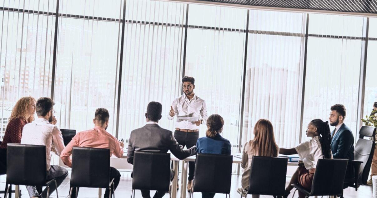 Ejecutivos en un programa de capacitación en inglés frente a un profesor en una mesa de reuniones