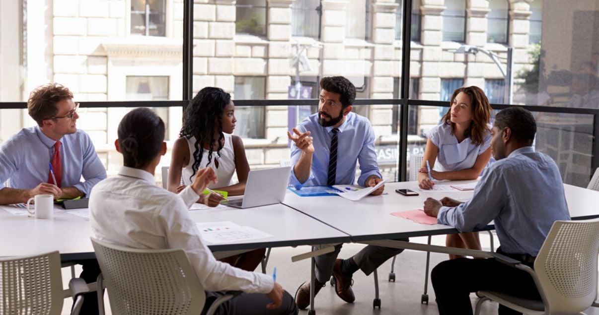 Ejecutivos y empleados en una reunion de trabajo en un buen clima organizacional luego de capacitarse en inglés con Wall Street English