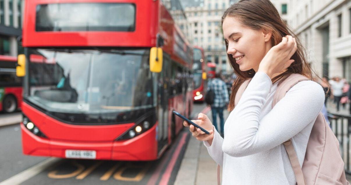 Joven estudiante con mochila rosa buscando direcciones en ingles en su telefono