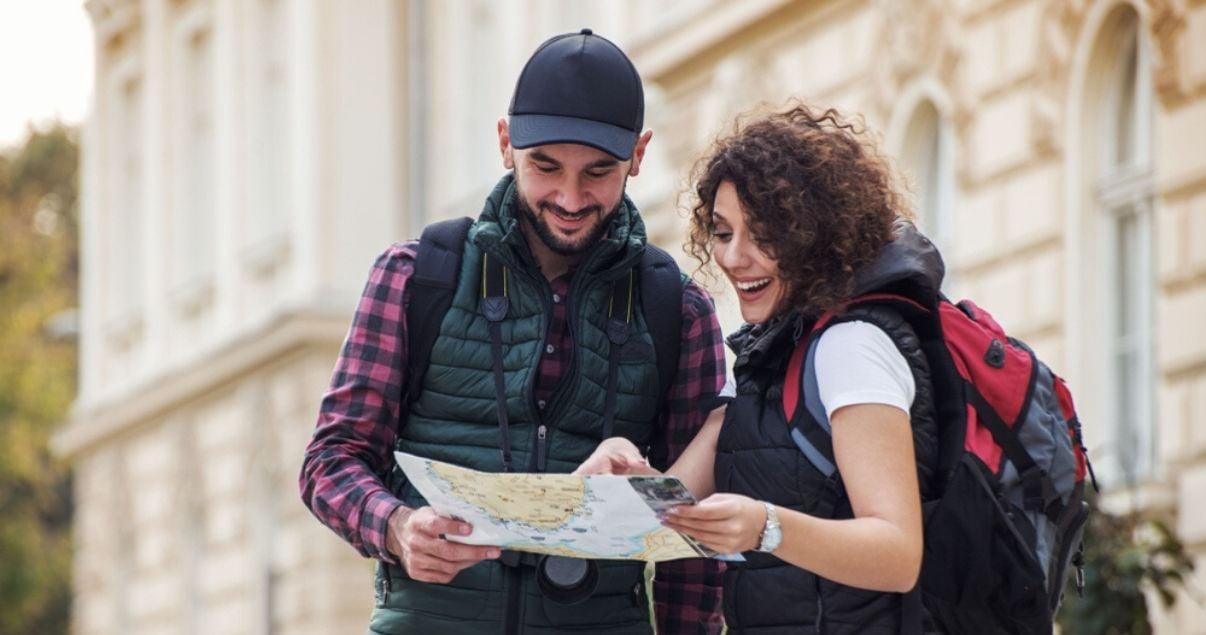 Hombre con gorra negra dando direcciones en inglés a una mujer joven con rulos