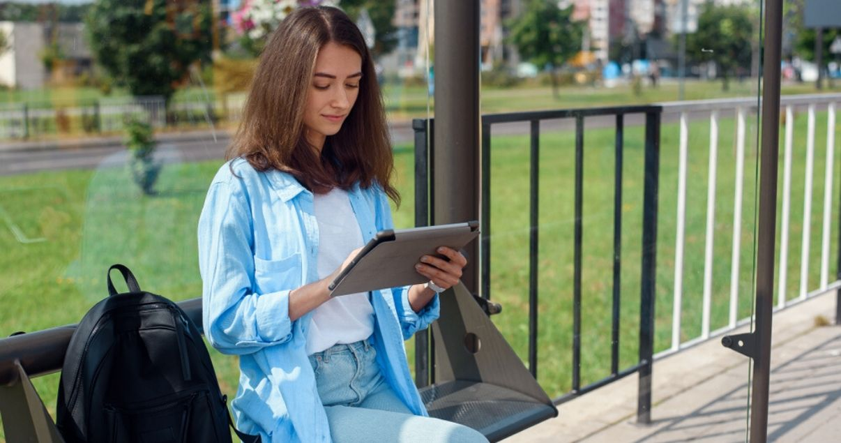 Mujer joven con pelo lacio y oscuro leyendo desde su tablet sobre presente perfecto en inglés