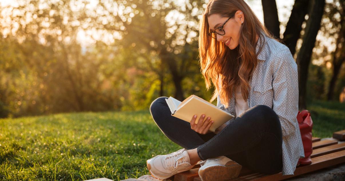 chica joven leyendo adjetivos en inglés en un libro en un parque.