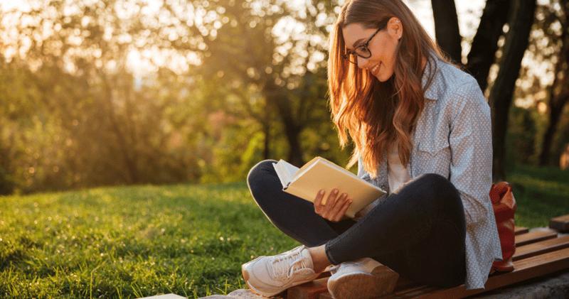 chica sonriente con camisa y anteojos leyendo un libro en una plaza al atardecer
