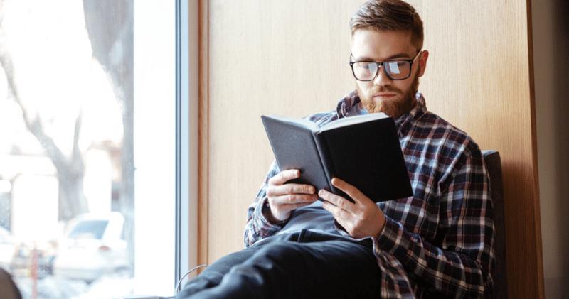 chico con anteojos y camisa leyendo un libro en inglés al lado de una ventana