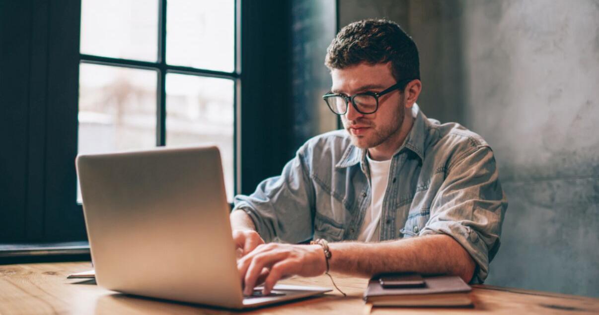 hombre-joven-mirando-laptop-para-aprender-inglés