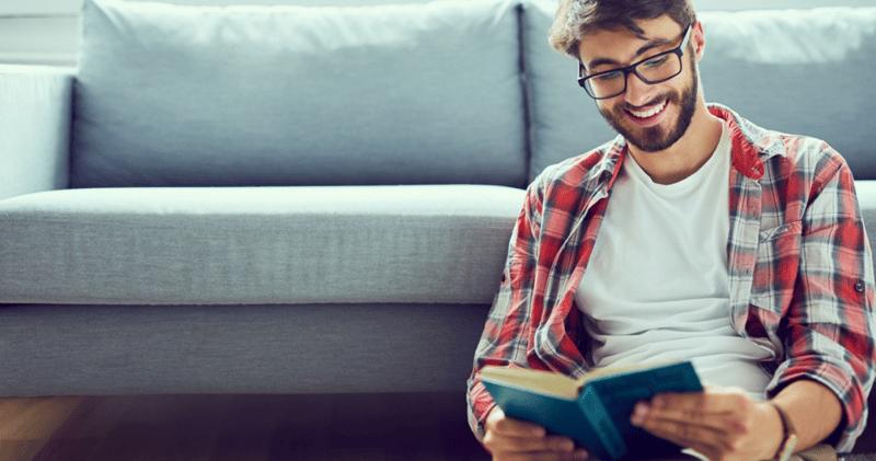 hombre con camisa y remera y anteojos negros leyendo libro en inglés en un sillón