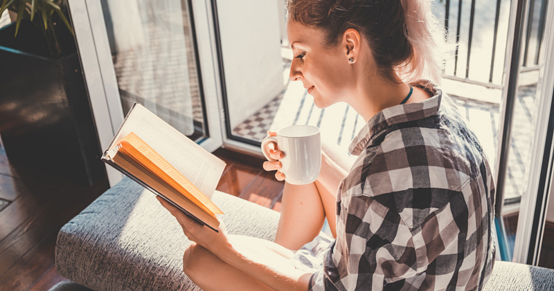 mujer con camisa y café leyendo libro en inglés en el balcón de una casa