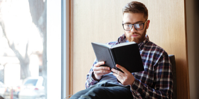 hombre con lentes leyendo un libro para hablar inglés con fluidez