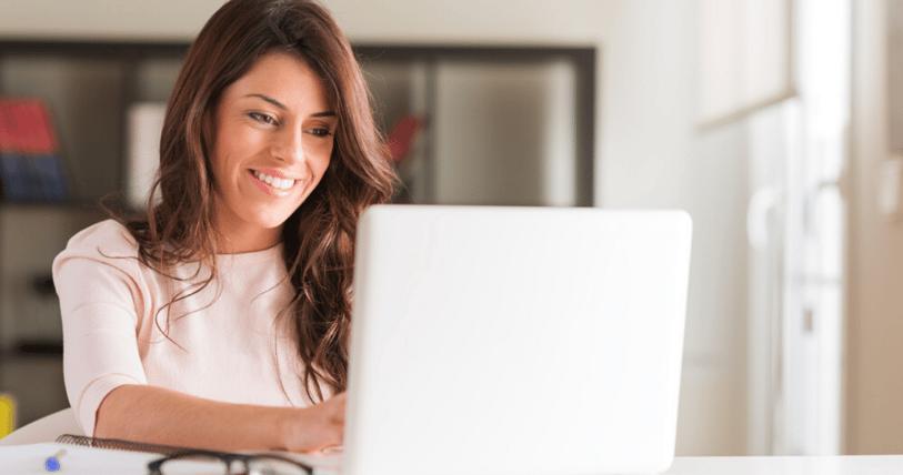 Mujer aprendiendo vocabulario en inglés feliz en su laptop con un anotador a su lado