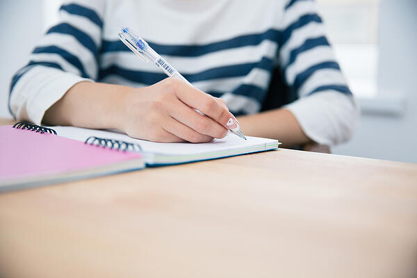 CLoseup portrait of a woman writing in notepad at office-1