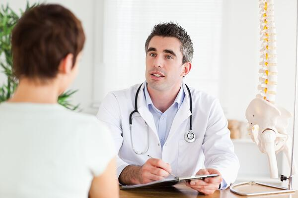 Male Doctor writing something down while patient is talking in a room