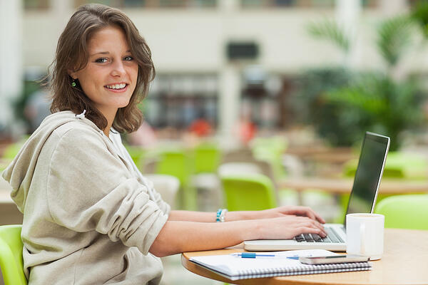 Side view portrait of a female student using laptop at cafeteria table
