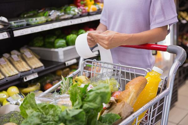 Woman reading her shopping list while pushing a shopping trolley