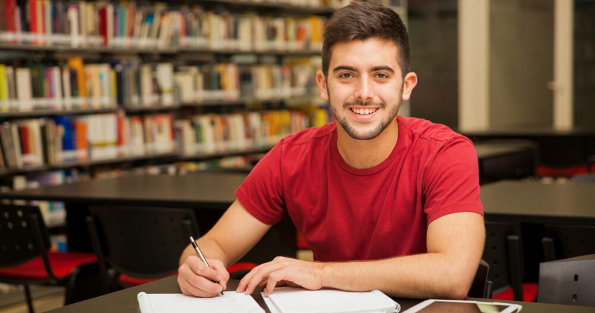 Un chico estudia en la biblioteca para ampliar su vocabulario en inglés.