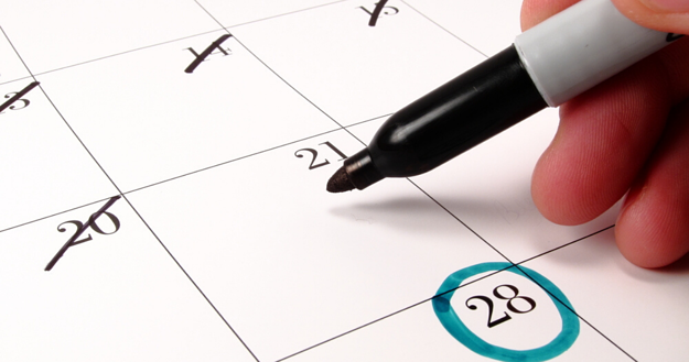 Una persona utilizando un calendario con el vocabulario en inglés necesario.