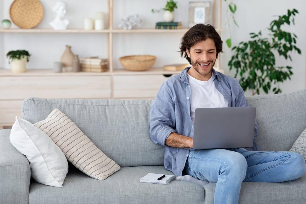Hombre aprendiedo en su sillon con su laptop a aprender a decir la fecha y hora desde su casa