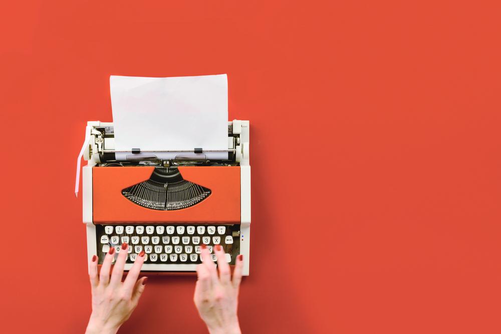 manos escribiendo en maquina de escribir historias en inglés