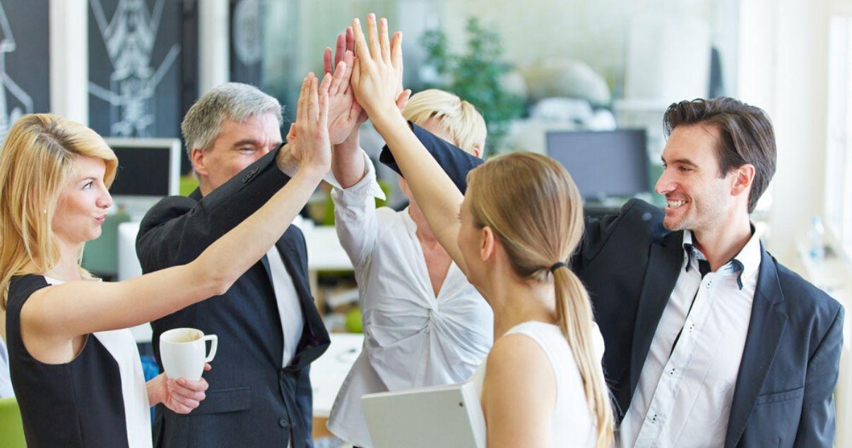 Ejecutivos y empleados de una importante empresa en un buen clima organizacional chocando manos luego de capacitarse en inglés con Wall Street English