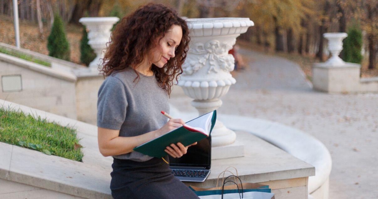 Mujero joven con rulos leyendo al aire libre sobre el presente perfecto en inglés