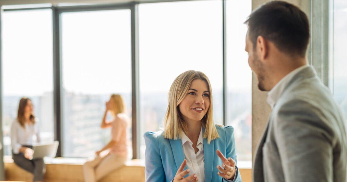 Mujer rubia conversando con gestos a un hombre de traje utilizando el vocabulario en inglés para principiantes
