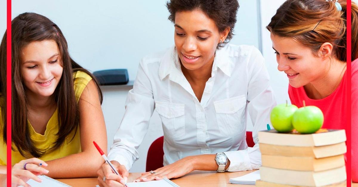Profesora de inglés enseñando reglas de gramática en inglés a dos niñas